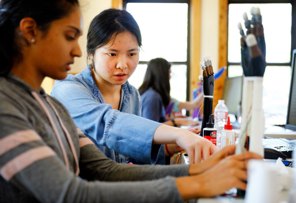 Girl Scouts Yuexi Tan (left), a junior at Richardson Berkner High, helps Esha Patel, a sophomore at Harmony Science Academy in Carrollton, build her prosthetic hand during a two-week course at the STEM Center of Excellence at Camp Whispering Cedars in Southwest Dallas on July 19, 2018. The two are working to get their robotics badge.