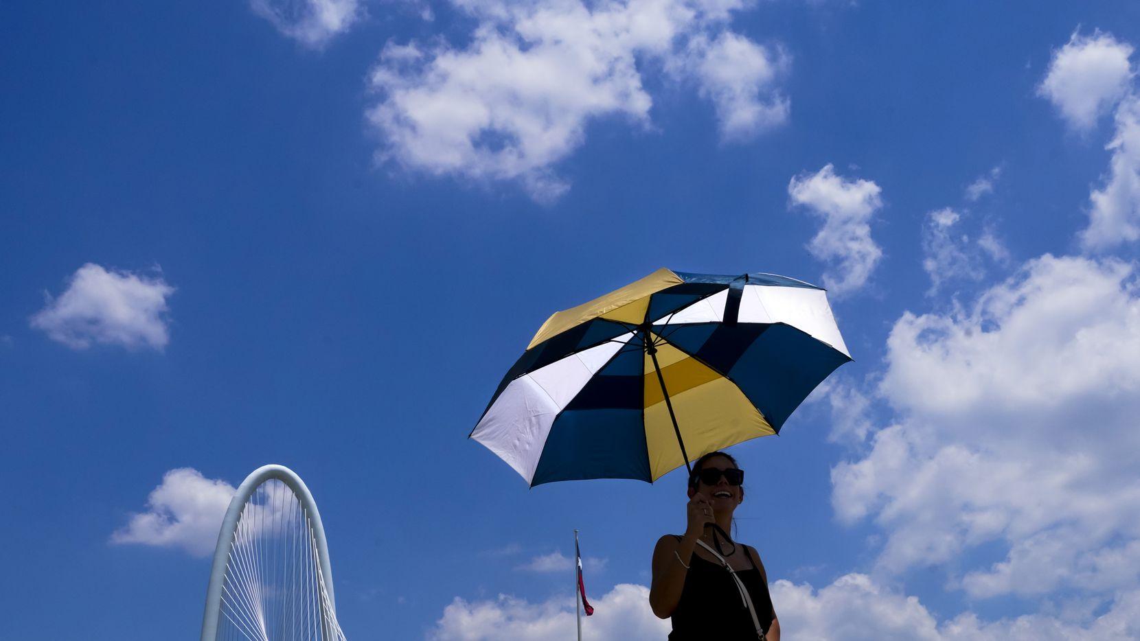 Vimarie Rivera se protege del sol en el puente Ronald Kirk, con el puente Margaret Hunt Hill. Esta semana se espera un clima soleado en el Norte de Texas.