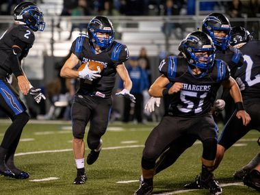 Dallas Christian junior running back TJ King (7) runs behind the blocks of Dallas Christian senior offensive lineman Jensen Barnett (51) and junior Kynan Gilreath (3) after taking the handoff from senior quarterback Zack Halland (2) in the first half of a high school football game against Fort Worth Christian on Friday, November 15, 2019 at Wheeler Field in Mesquite, Texas.