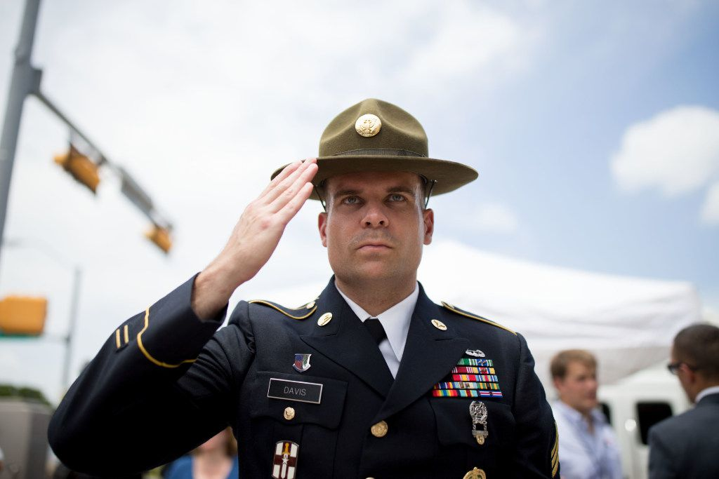 Retired Army combat medic Chandler Davis stood saluting the memorial for slain Dallas police officers at Dallas police headquarters on July 9, 2016, two days after the police ambush in downtown Dallas. (File Photo/Staff)