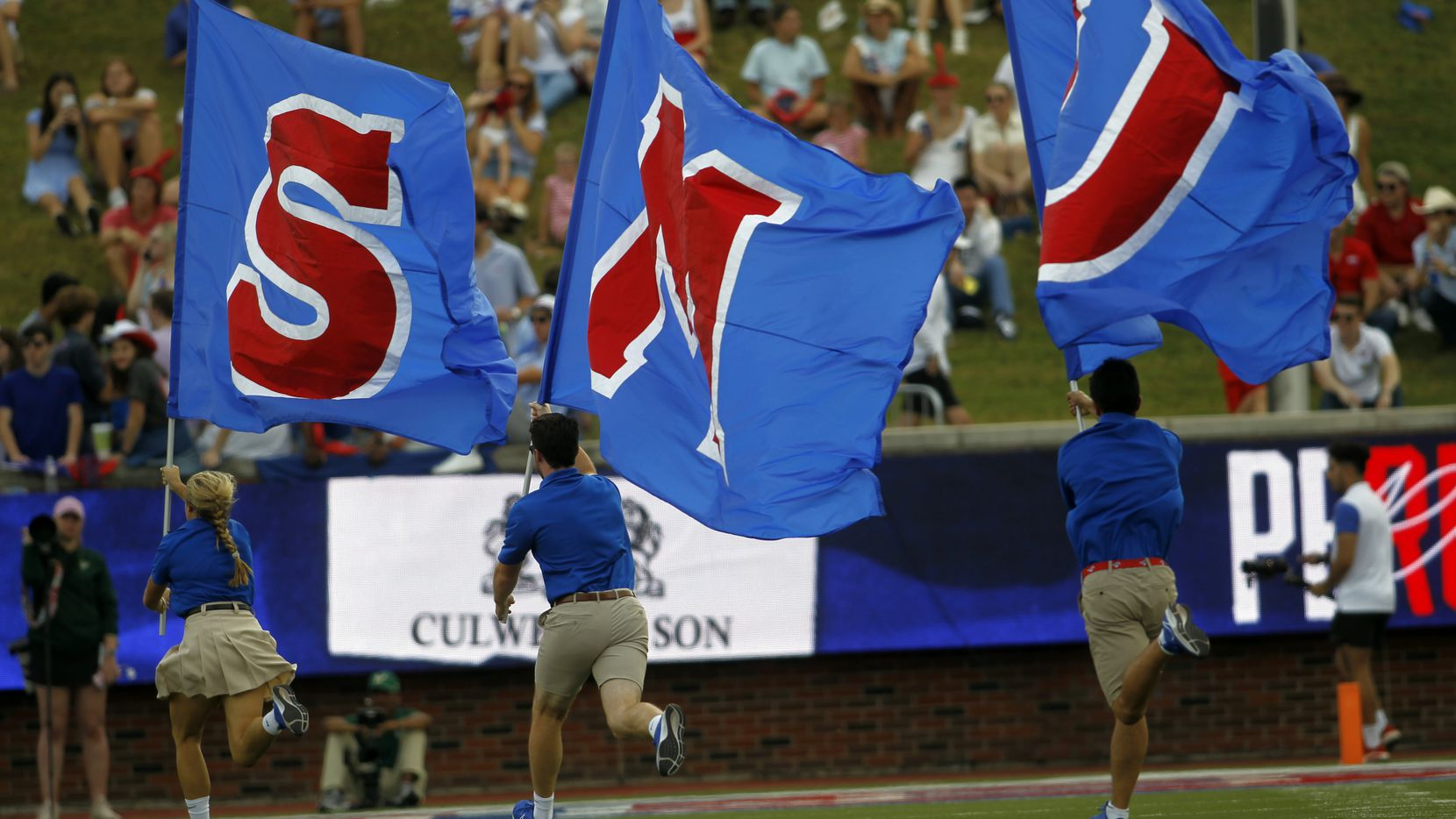 SMU spirit group members race across the field following a first half scoring drive in their game against South Florida. The two teams played their NCAA football game at SMU's Ford Stadium in Dallas on October 2, 2021.
