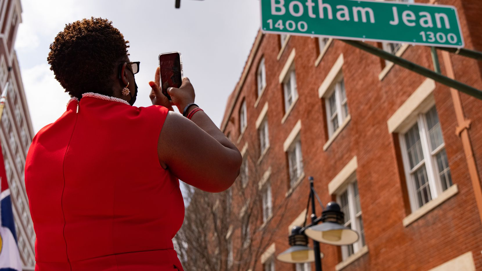 Botham Jean's mother, Allison Jean, takes a photo of a sign bearing his name at a ceremony to redub a four-mile stretch of Lamar Street in his honor Saturday, March 27, 2021.