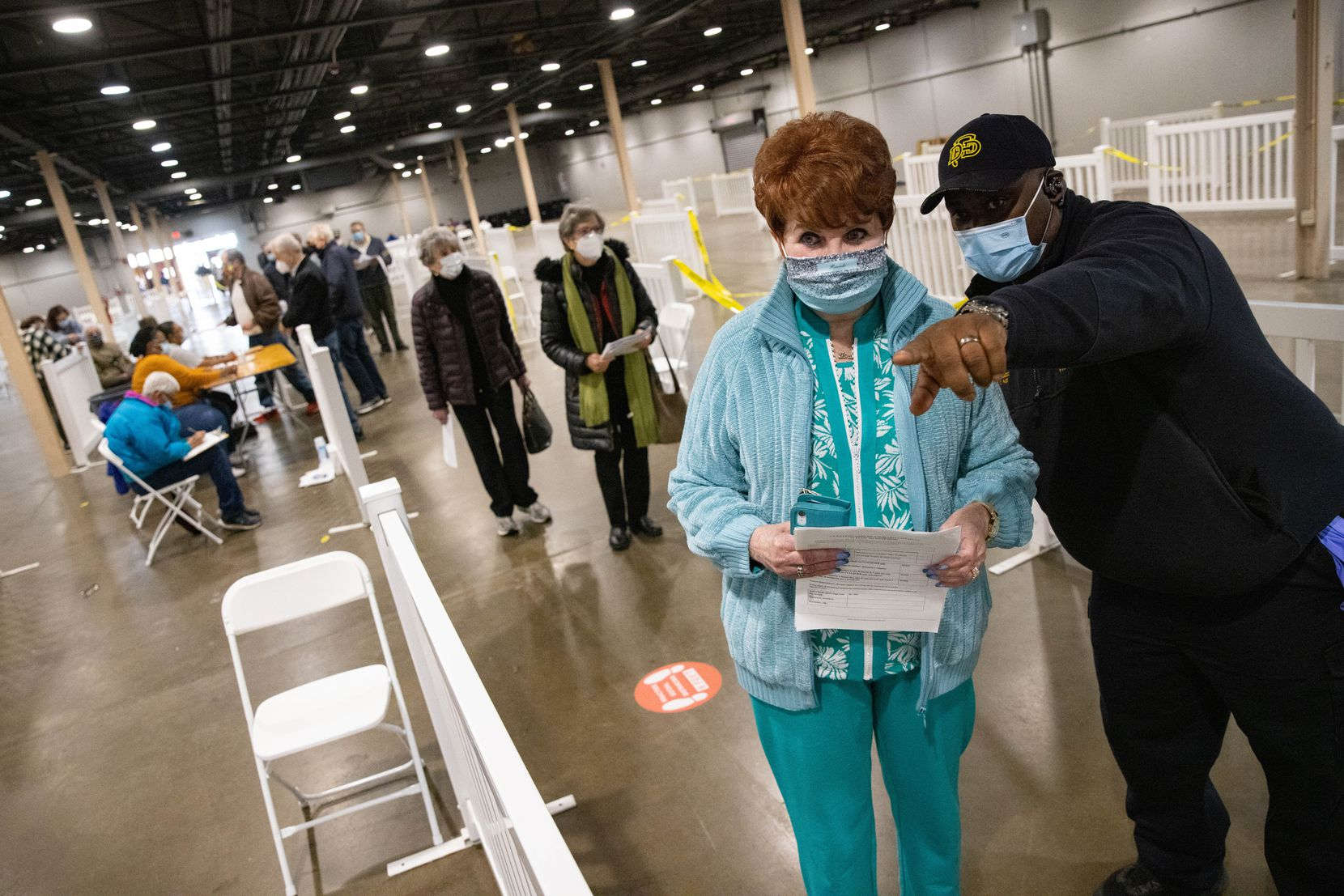 Lt. Clinton Page of Dallas Fire-Rescue instructs Brenda David, 75, where to wait for the COVID-19 vaccine after she verified her information at Fair Park in Dallas on Thursday, Jan. 14, 2021. David said she dressed in layers in case there was a long line to get inside.