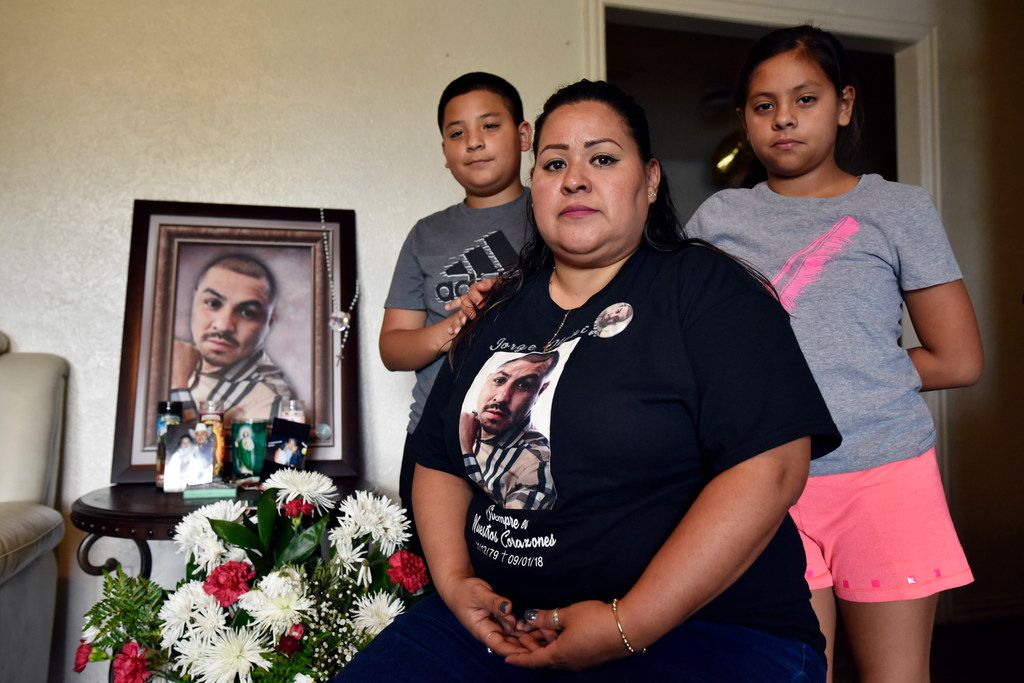 Vanessa Olguín with her children, Jorge, 12, and Amy, 10, pose with a portrait of her husband, Jorge Olguín, at their home in southern Dallas.