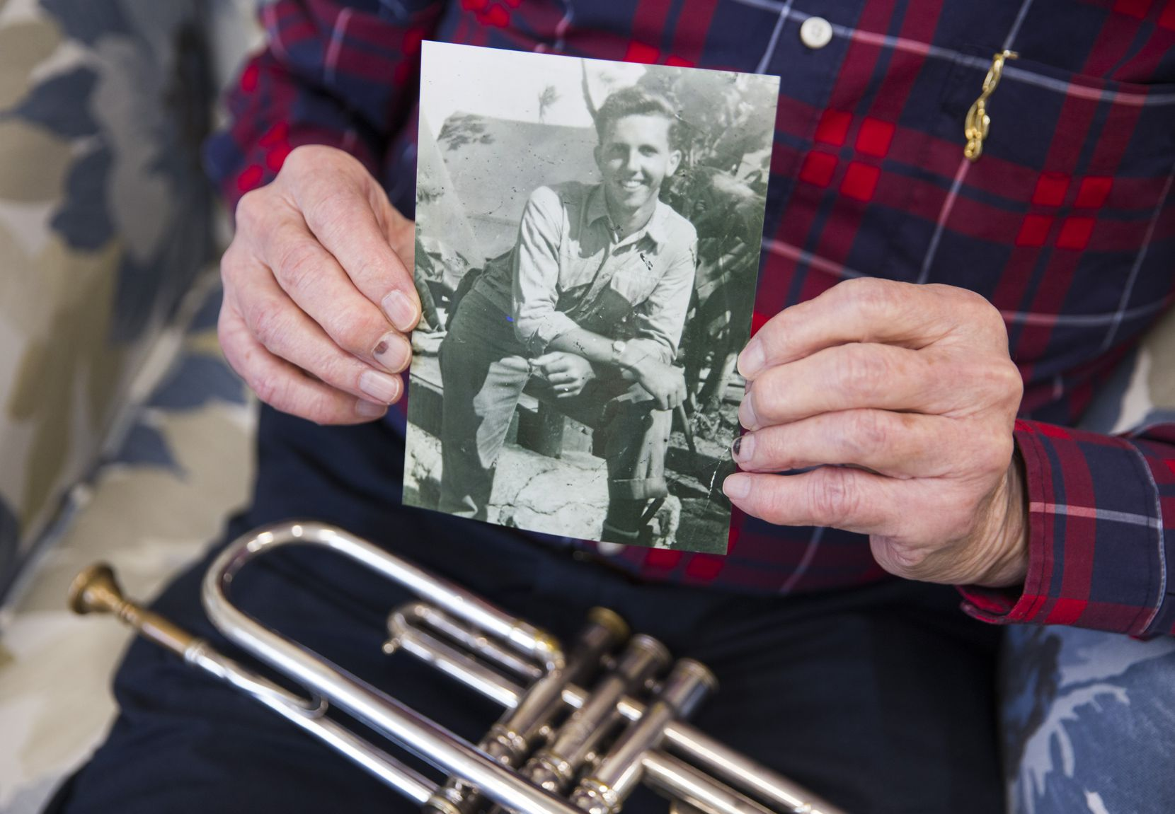 John Gould holds a photo of himself from his World War II days and his beloved trumpet, an instrument he has played since he was a child.