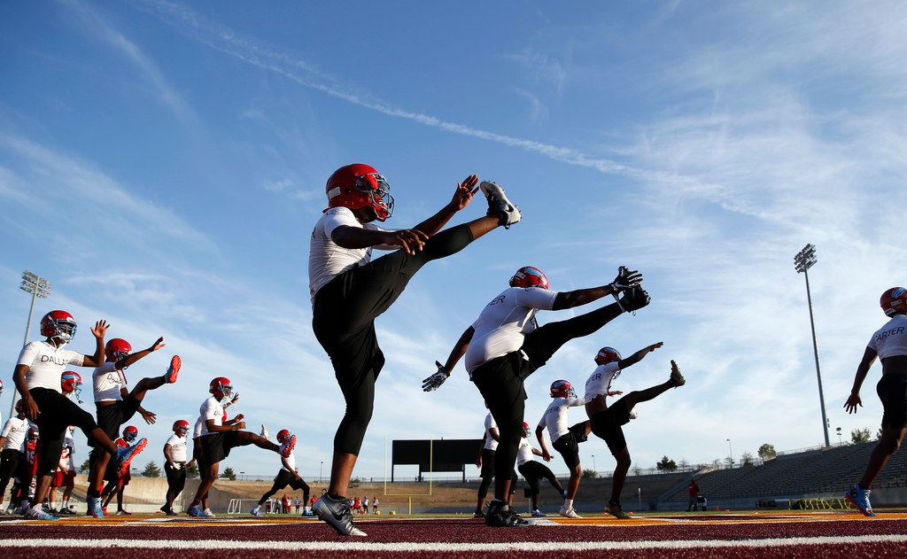 The Carter High School football team stretches during practice at Kincaide Stadium in Dallas, on Monday, August 6, 2018.
