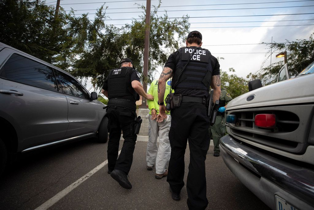 U.S. Immigration and Customs Enforcement (ICE) officers escorted a man in handcuffs during an operation in Escondido, Calif., earlier this month.