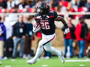 LUBBOCK, TEXAS - NOVEMBER 16: Running back Ta'Zhawn Henry #26 of the Texas Tech Red Raiders runs the ball during the first half of the college football game against the TCU Horned Frogs on November 16, 2019 at Jones AT&T Stadium in Lubbock, Texas.