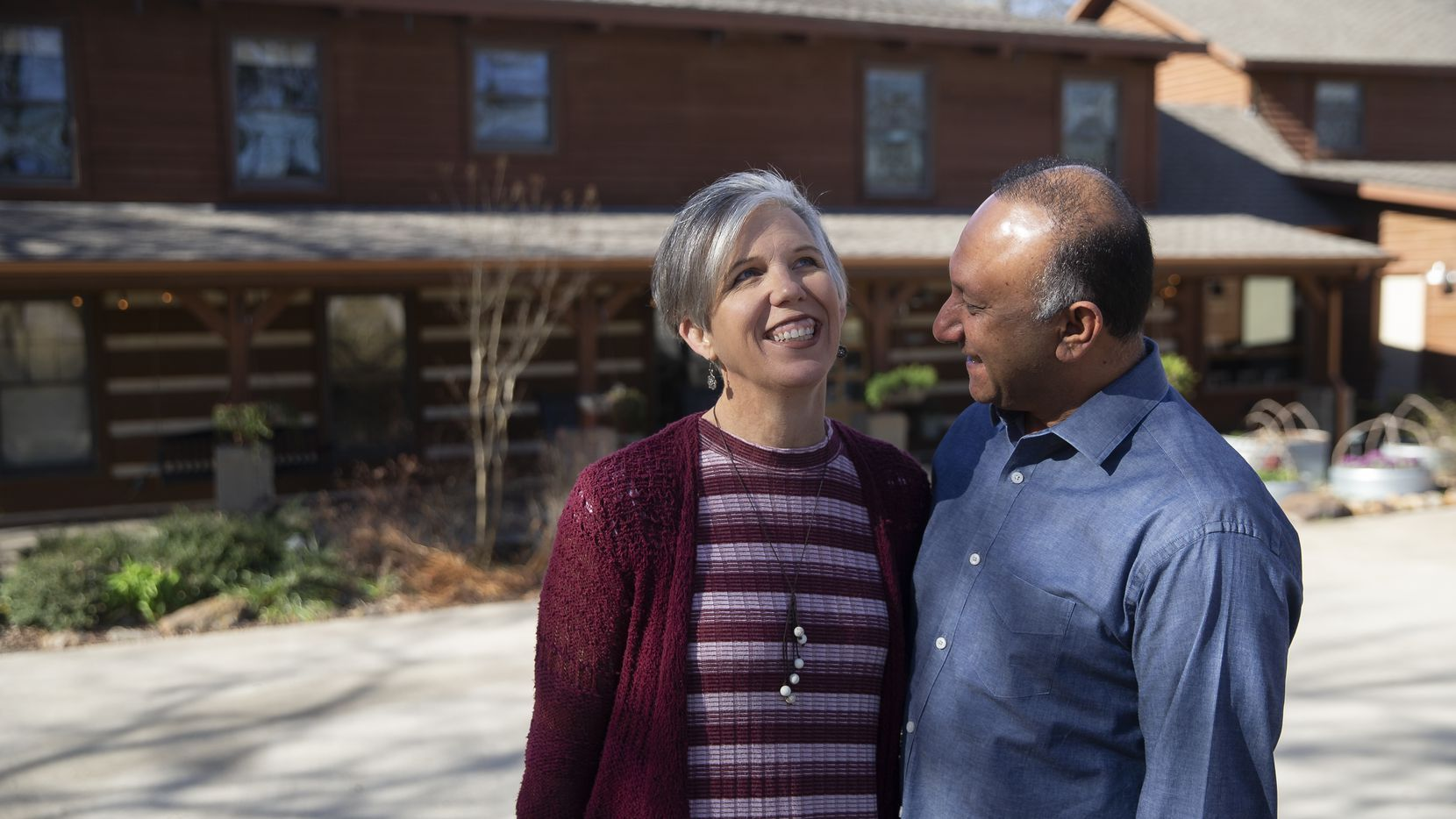 Ali Master and his wife, Judy, laugh while posing for photos at their log cabin home in Rockwall.