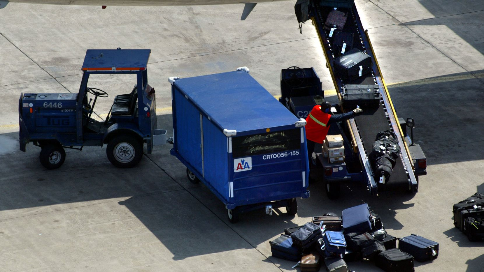 A baggage handler unloads luggage from an American Airlines flight arriving at DFW International Airport.