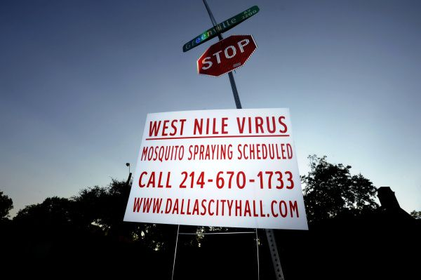 A sign at Monticello and Greenville avenues in Dallas announces scheduled mosquito spraying.