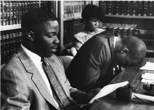 Gary Edwards, (left) the former Carter HS football player, cries as he reads a statement as teammate Derric Evans (right) lays his head on the table during a news conference at their attorney's office  on July 8, 1989. The two are charged with armed robbery. Background is Evan's mother Peggy Evans.