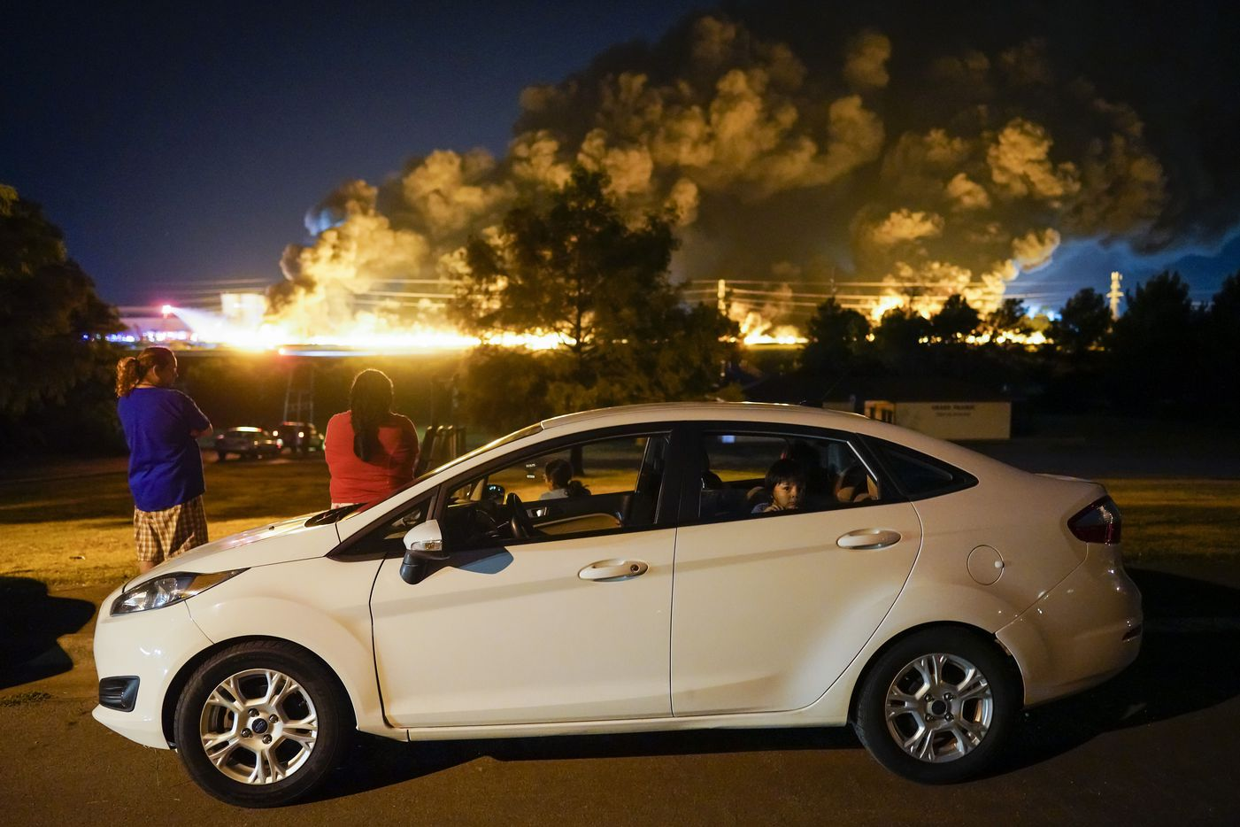 People watch from Tyre Park as fire crews battle a massive blaze in an industrial area of Grand Prairie in the early morning hours of Wednesday, Aug. 19, 2020.