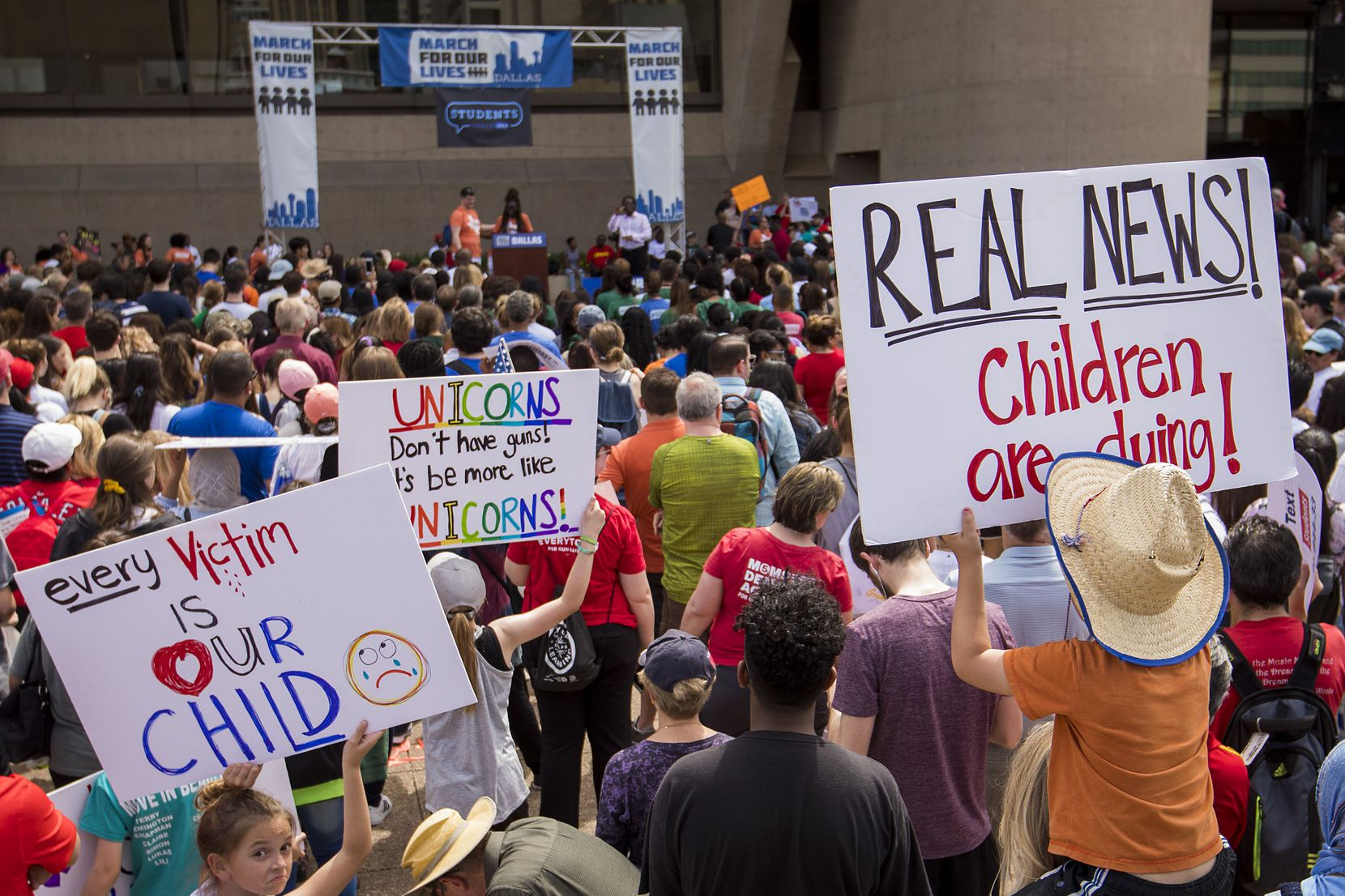 """Brooks Herr, 4, holds a sign reading """"Real News! Children are dying!"""" as he listens to speakers from atop the shoulders of his mother Ariel Herr."""