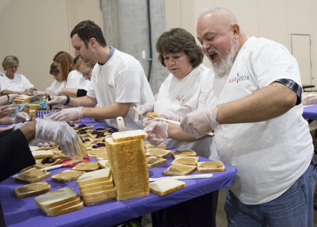 Rushing to help create 38000 PB&J sandwiches in one hour to break the Guinness World Record for the highest number of PB&Js made in one hour in one room, volunteer Walter Melendez quickly grabs bread before spreading peanut butter onto it.
