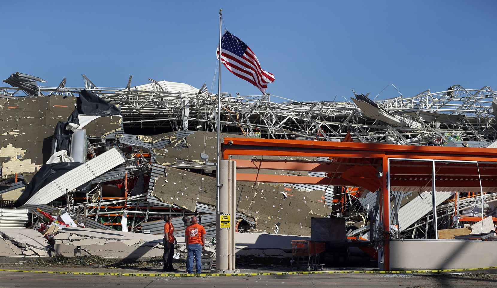 The Home Depot employees A.J. Kobena (center) raises the U.S. flag on the slightly bent flagpole outside the destroyed store on N. Central Expressway in Dallas, Monday, October 21, 2019. Jining him were fellow employees Jonathan Shields and Jordan Jasper. A tornado tore through the entire neighborhood knocking down trees and ripping roofs from homes.