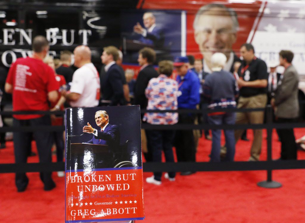 """Texas Attorney Greg Abbott signs his new book, """"Broken But Unbowed,"""" during the 2016 Texas Republican Convention in May 2016 at the Kay Bailey Hutchison Convention Center in Dallas."""