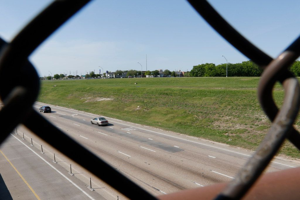The chain link fence of a pedestrian bridge over LBJ Freeway frames undeveloped land on the north side of the freeway near Skillman Street.  The pedestrian bridge connects the south side of the freeway to the DART  LBJ/Skillman station. (Ron Baselice/The Dallas Morning News)