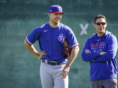 Texas Rangers pitcher Brock Burke chats with general manger Jon Daniels as they watch a bullpen session during a spring training workout at the team's training facility on Sunday, Feb. 16, 2020, in Surprise, Ariz.