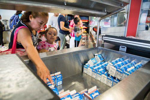 María Vargas (izq.) ayuda a Brianna García con su refresco durante la apertura del programa de comidas de verano del distrito de Dallas.