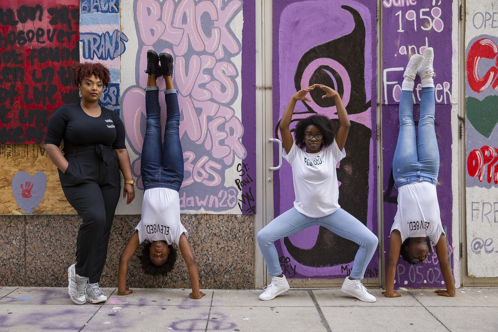 (From left) Dance director Shantrail White poses with members of Elev8ed Elites, co-captain Sha'kyra Roberts, 13, Zaria Fisher, 10, and Janyiah Cooks, 12, on June 27, 2020 in downtown Dallas. Elev8ed Elites is an all girls dance team that shot a video downtown in response to police brutality shortly after George Floyd died. (Juan Figueroa/ The Dallas Morning News)