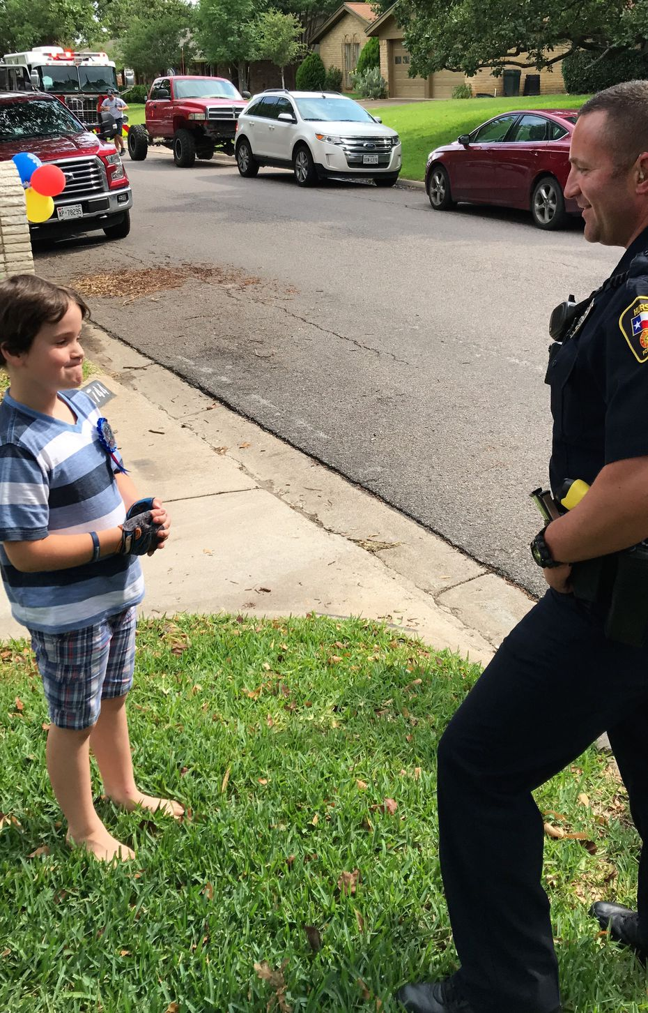 Graham Day, 8, talks with a Hurst police officer who celebrated his birthday with him.