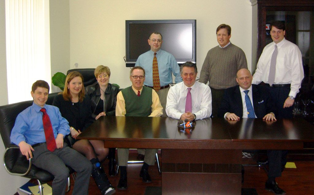 Konstantin Kilimnik, an elusive figure under indictment for alleged witness tampering by Special Counsel Robert Mueller, is seen seated on the far left in a March 2006 photo obtained by The Associated Press as part of a collection of internal corporate memos and business records from the international political consulting offices of Donald Trump's ex-campaign chairman, Paul Manafort. Mueller has indicated that Kilimnik is in Russia and has ties to Russian intelligence, which Kilimnik disputes. The photograph represents one of the few images known to exist of Kilimnik.