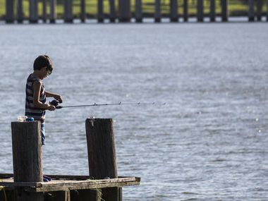 Jovanni Ledezma, 7, fishes from a pier at John Paul Jones Park along Lake Ray Hubbard in Garland, Texas, on Saturday, July 18, 2020.
