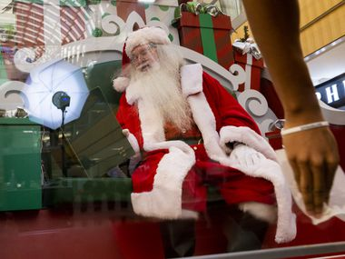Santa Claus sits behind a screen as it gets desensitized at the Galleria in Dallas on Sunday, Dec. 6, 2020.