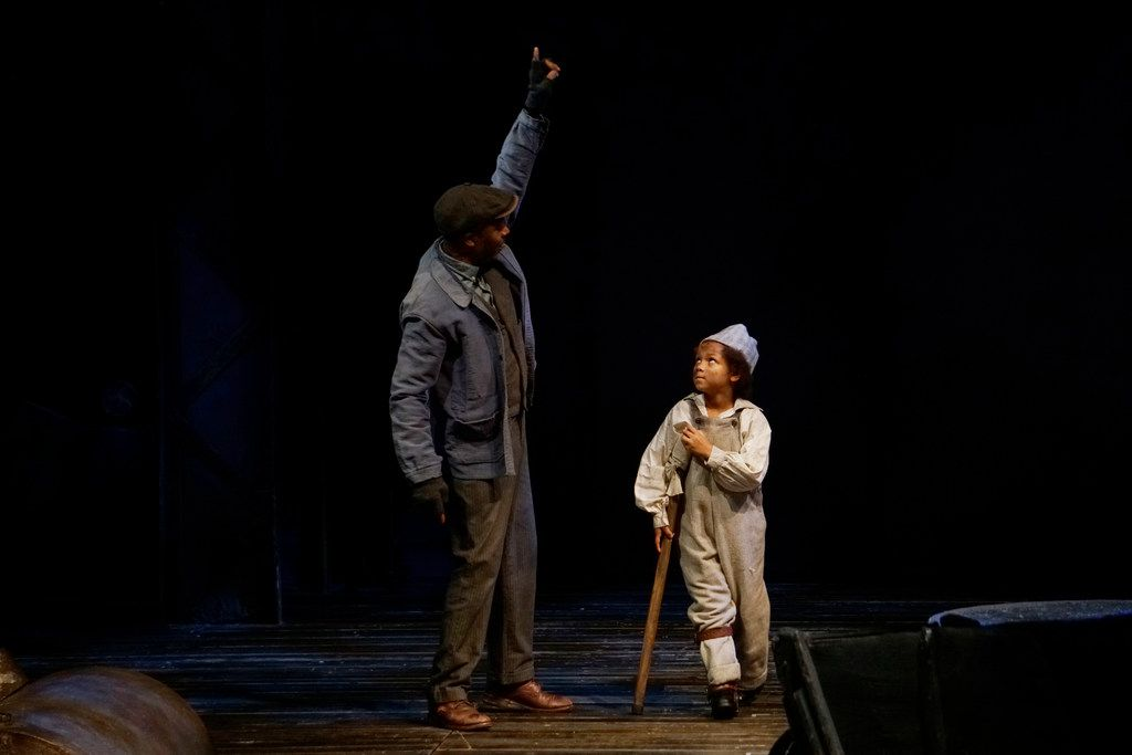 """Jahi Kearse as Bob Cratchit and Olivia Meredith (alternating with Cooper Carter) as Tiny Tim in Dallas Theater Center's """"A Christmas Carol""""  at the Wyly Theatre."""