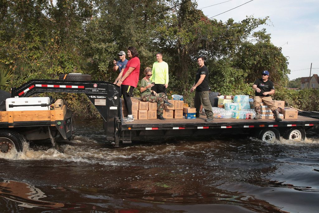 Volunteers with Merging Vets and Players distribute food water and pet food to flood victims after the town was inundated when torrential rains pounded Southeast Texas following Hurricane and Tropical Storm Harvey causing widespread flooding on Sunday in Orange, Texas. (Photo by Scott Olson/Getty Images)