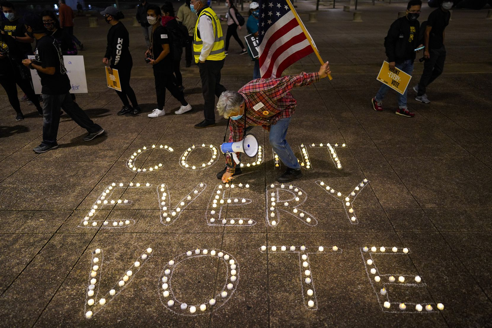Benny De La Vega lighted candles to highlight the prevailing sentiment during a rally at Dallas City Hall on Nov. 4, the day after the election. Participants represented several organizations, and speakers addressed the crowd of about 100 in English and Spanish.