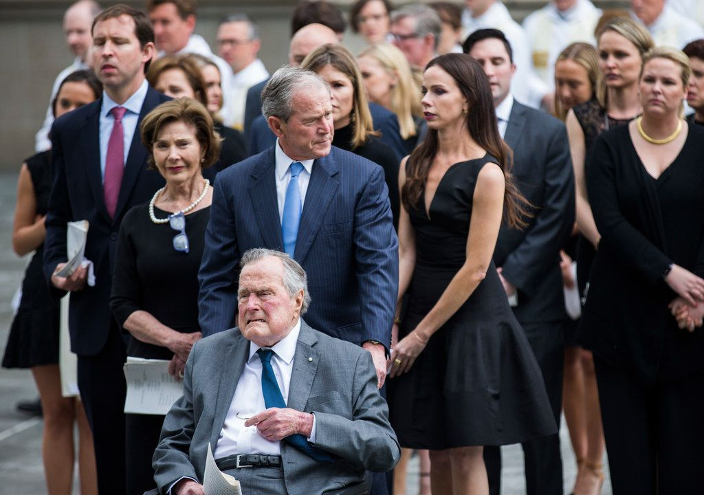 Former President George W. Bush escorts his father, former President George H.W. Bush, out of St. Martin's Episcopal Church in Houston. They had attended the funeral for Barbara Bush, the older man's wife, with family members including former first lady Laura Bush (left).