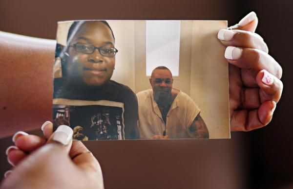 Talia Clay, who holds a photo of her son, Jordan King (left), and his father and her fiance Christopher King, says she'd marry him today but will wait until he's released from prison.