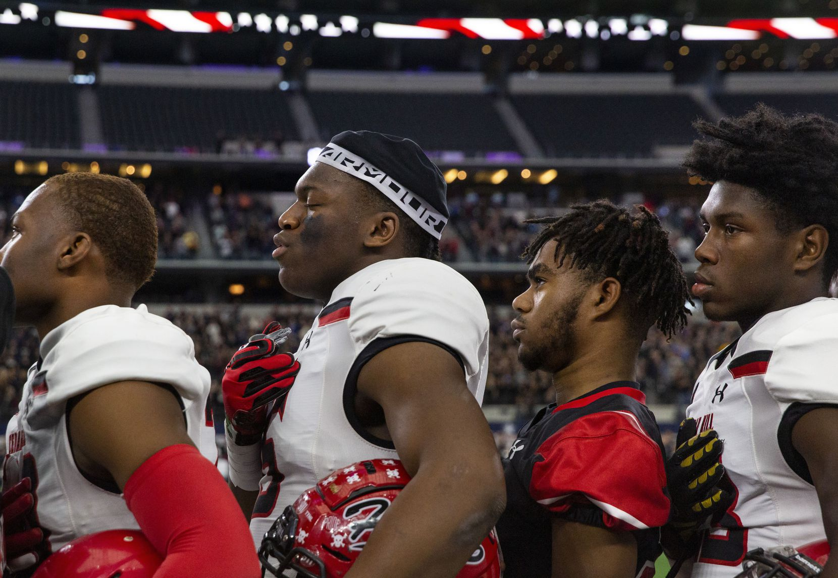 Cedar Hill players pray during the National Anthem prior to the game against Denton Guyer in the Class 6A Division II area-round high school football playoff game at the AT&T Stadium in Arlington, Texas, on Saturday, November 23, 2019. Denton Guyer beat Cedar Hill 50-41 in a major comeback after trailing by 27 points at halftime.