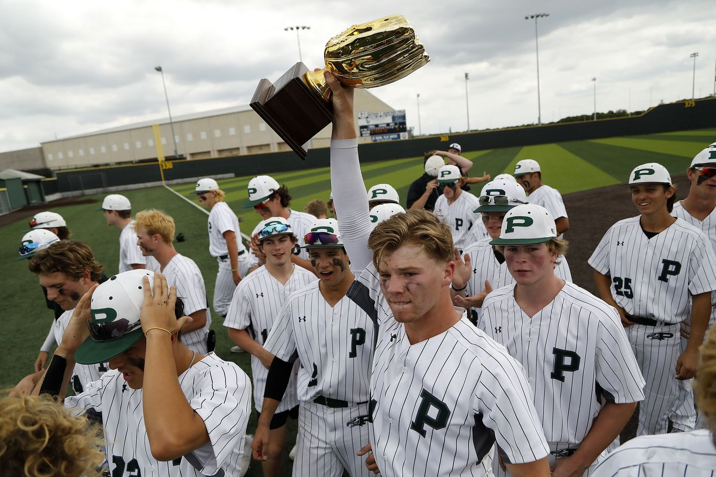 Prosper catcher Easton Carmichael (11) hoists up the area trophy after his team's victory as Prosper High School hosted Arlington Martin High School in a series final 6A Region I area round playoff game on Saturday afternoon, May 15, 2021. (Stewart F. House/Special Contributor)
