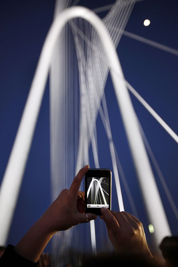 Susette Cody, of Dallas, photographs the bridge, using her iPhone during the second day of the big celebration for the inauguration of the Margaret Hunt Hill Bridge, in Dallas, on March 3, 2012. ( Kye R. Lee / The Dallas Morning News )