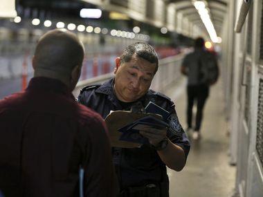 Un agente de Aduanas y Protección Fronteriza supervisa los documentos de una personas en un puente internacional entre Laredo, Texas y Nuevo Laredo, México.