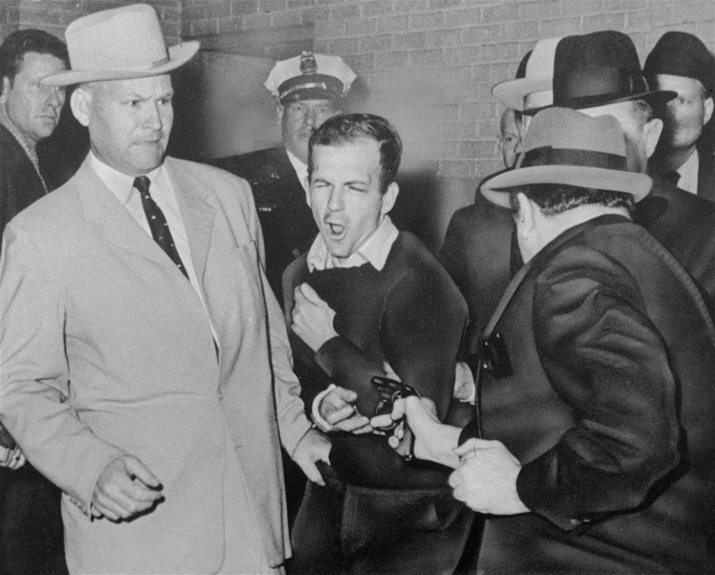 Lee Harvey Oswald is shot by Dallas night club owner Jack Ruby at point blank range in a corridor of Dallas police headquarters on Nov. 24, 1963. At left is Detective Jim Leavelle.