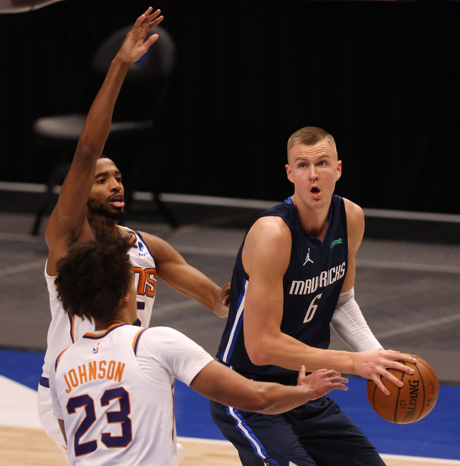 Dallas Mavericks forward Kristaps Porzingis (6) looks to shoot as Phoenix Suns forward Mikal Bridges (25) and Phoenix Suns forward Cameron Johnson (23) defend during the first quarter of play at American Airlines Center on Monday, February 1, 2021in Dallas. (Vernon Bryant/The Dallas Morning News)