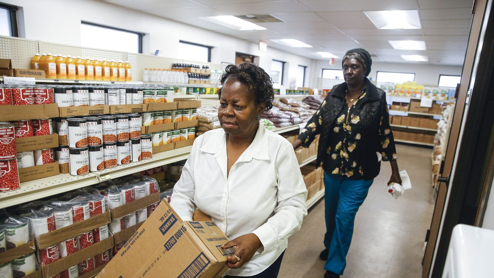 Betty Rayson, left, and Gladys Coleman stock food pantry shelves at Harmony Community Development Corporation on Thursday, Nov. 21, 2019 in Dallas. (Ryan Michalesko/The Dallas Morning News)