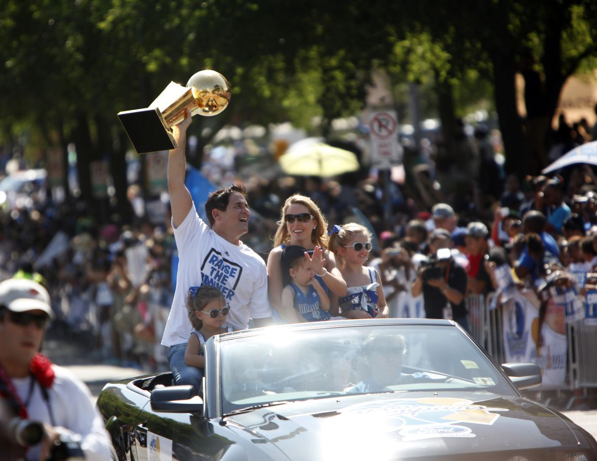 Accompanied by his family Dallas Mavericks owner Mark Cuban hoists the Larry O'Brien NBA Championship Trophy in the air while riding in the 2011 Dallas Mavericks NBA World Championship Celebration Parade down Young Street in Dallas on June 16, 2011. The Dallas Mavericks beat the Miami Heat in the 2011 NBA Finals. (Sonya N. Hebert/The Dallas Morning News) / mavsmavsmavs /