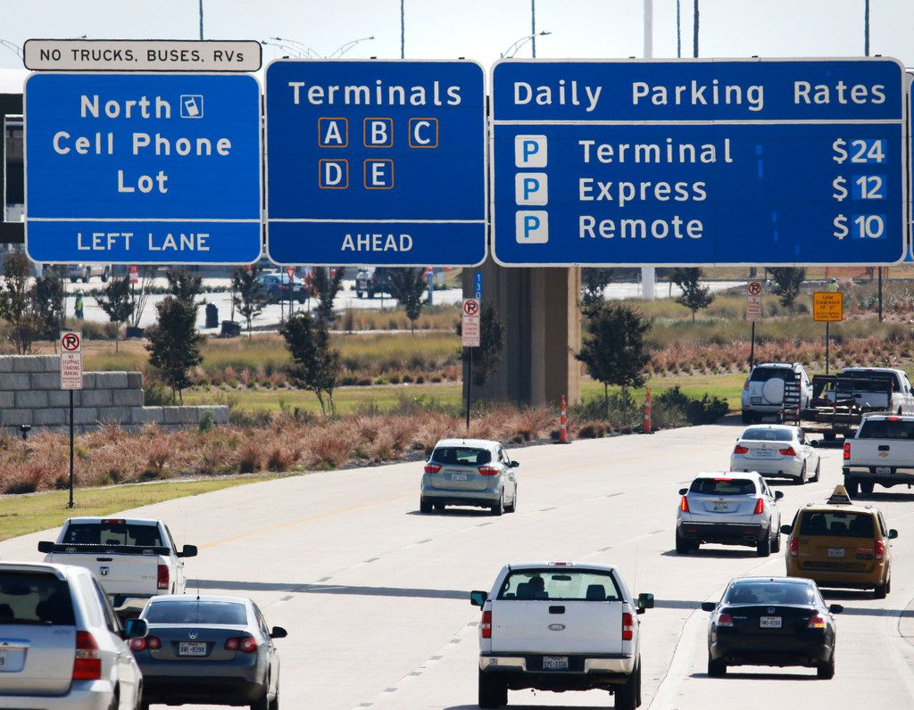 Road signs on Highway 114 inform drivers where the cellphone lot is located before the northbound entrance to DFW International Airport on Nov. 10, 2017. This will allow people to park and wait near the entrance of the airport without incurring parking fees.