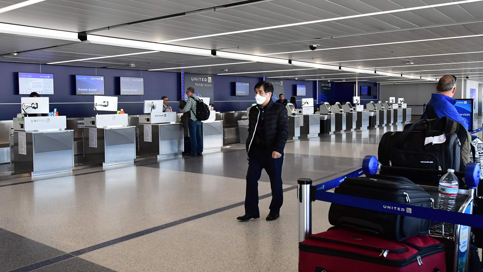 A man wears a facemask as he walks past empty United Airlines check-in counters at Los Angeles International Airport.