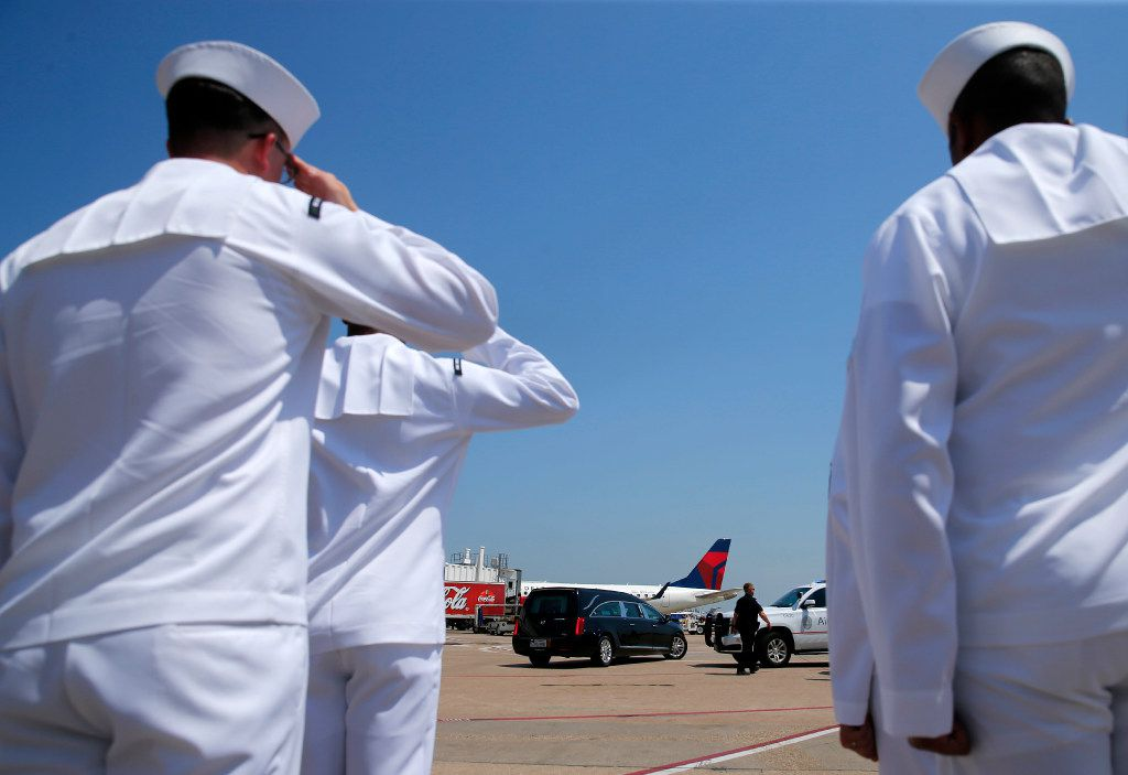 Members of the Naval Air Station Joint Reserve Base Fort Worth Honor Guard Team salute as the remains of Navy Seaman 1st  Class George A. Coke Jr. of Arlington are driven away in a hearse after arriving on a commercial flight at DFW International Airport.