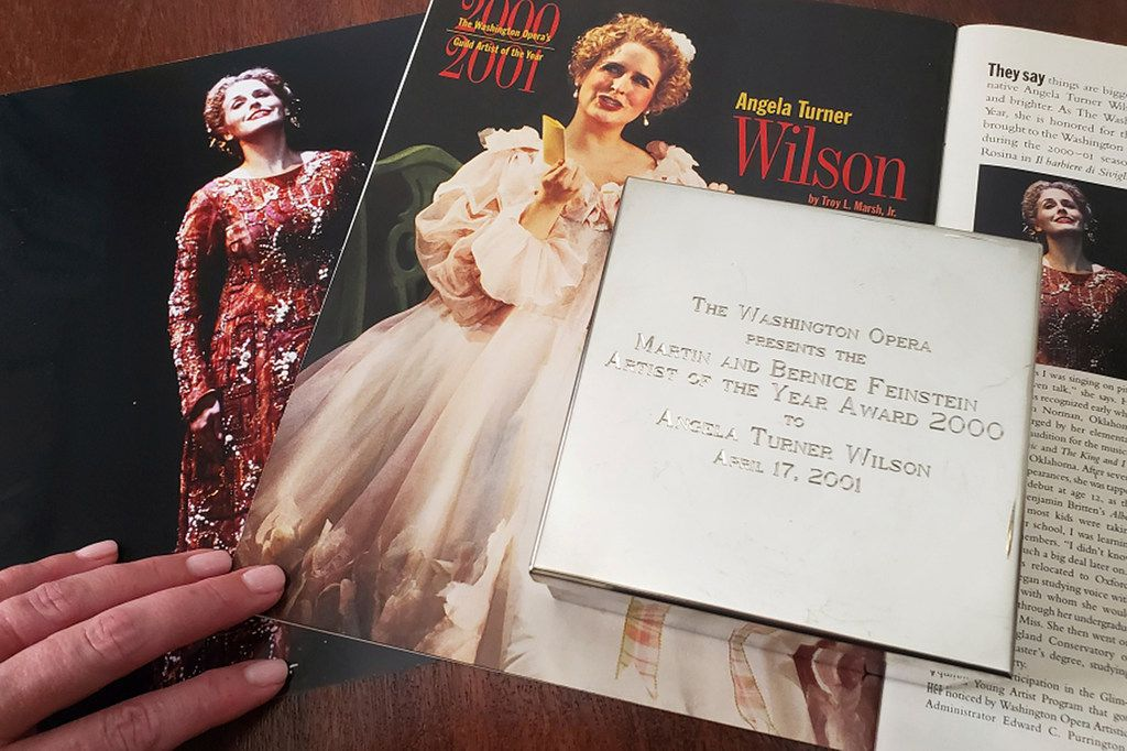 In this Tuesday, Sept. 2, 2019 photo provided by opera singer Angela Turner Wilson, she displays her 2000 Artist of the Year award from the Washington Opera next to a photo of herself from a 1999 performance of Le Cid, left, and a magazine article in a Washington Opera magazine, at her home in Texas.