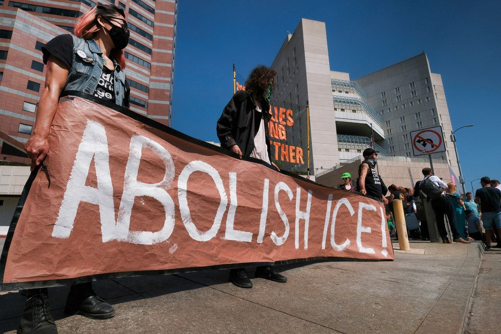 """Protesters display a sign that reads """"Abolish ICE"""" during a rally in front of the Immigration and Customs Enforcement facility in downtown Los Angeles on July 2, 2018. Protesters who were blocking the entrance to the facility were led away in handcuffs. A group of 17 protesters sat down in the street, blocking the entrance to the facility. The protesters, including faith and community leaders, locked arms and chanted, """"Shut down ICE!"""""""