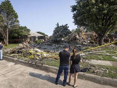 """Theo Laskaris, center, and Virginia French, right, examine the damage at the site of a house explosion on the 4400 block of Cleveland Drive in Plano, Texas, on Tuesday, July 20, 2021. The explosion, which happened Monday, left six people hospitalized and was likely due to an isolated gas leak, fire investigators said. French lives nearby, and said she thought the explosion was thunder during an afternoon storm. """"This is terrifying, I'm in shock,"""" French said. """"It could happen to anybody. How am I supposed to know if I have a gas leak I don't know about? It just scares me."""""""