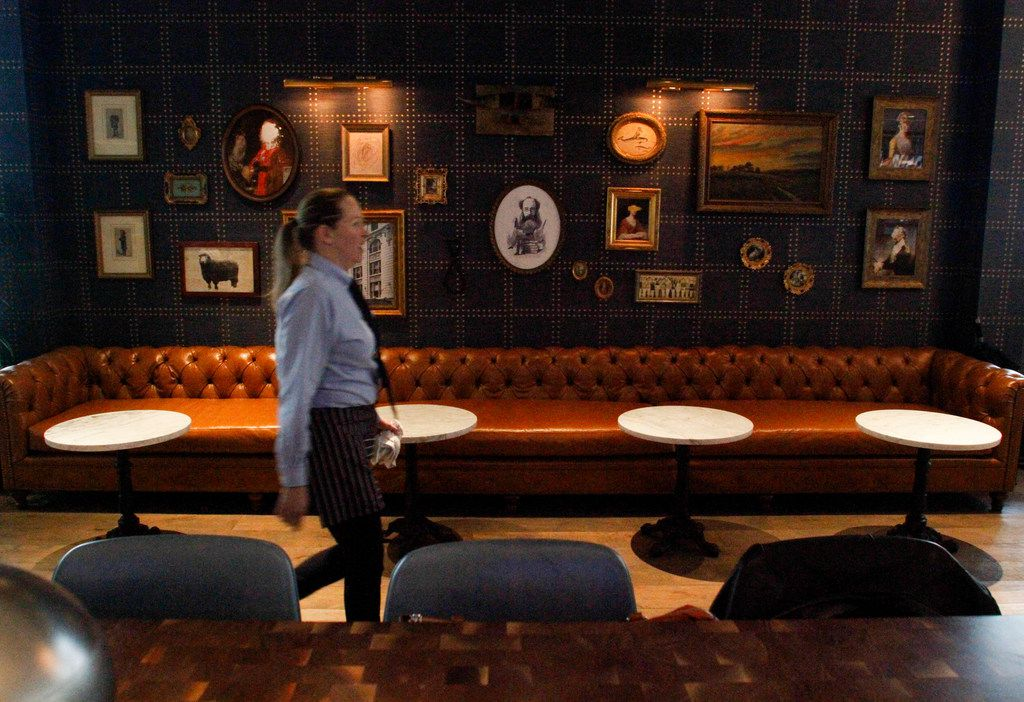 Server Tina Caraway walks through the bar and waiting area in the front of The Henry restaurant in uptown Dallas.