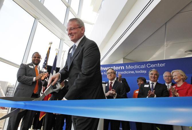 Dr. John Warner cut a ribbon during the dedication ceremony of William P. Clements Jr. University Hospital at UT Southwestern Medical Center on Thursday.